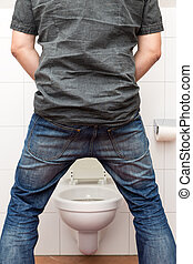 man peeing standing up in the restroom - a man peeing...