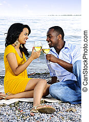 Happy couple having wine on beach - Young romantic couple...