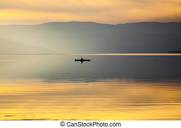 Lone Kayaker on Still Water in Mountains