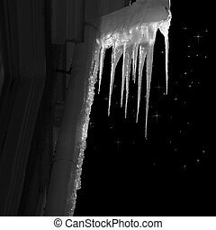 Icicles on pipe on facade of building on starry night