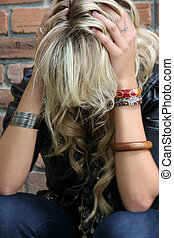 Depression - Unhappy blond young woman holding her head in...