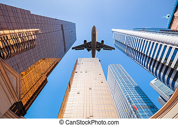 upward view of airplane and modern building background in...