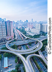 a highway interchange in guangzhou at dusk with vehicles...