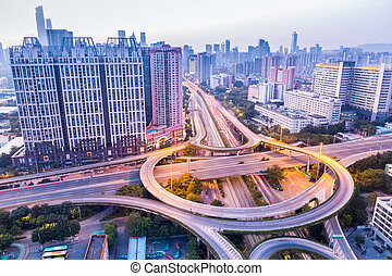 a highway interchange in guangzhou at dusk with modern city...