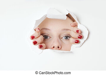 young woman peeking through hole in paper wall