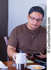 Hispanic Middle Age Male Using Calculator At Dining Table