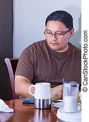 Middle Age Latino Male Writing In Thought - Middle Age...