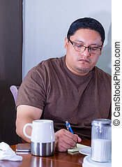 Man Seated At Dining Table Taking Notes On Paper Notepad