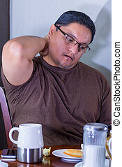 Male Holds Neck While Multitasking - Male Seated at Table...