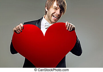 Laughing young man holding a heart