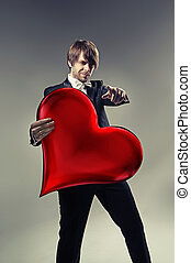 Handsome boy holding a cartoon heart - Handsome boy holding...