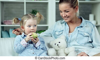 Apple a Day - Close up of mother habituating daughter to...