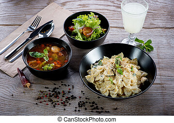Italian dinner with pasta, soup minestrone and salad on...