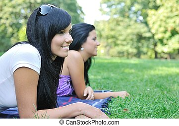 Two smiling friends lying outdoors in grass