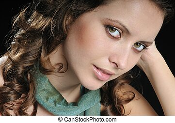 Portrait of young dreamy woman on black