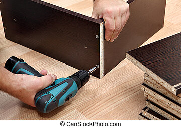 Furniture assembly using a cordless screwdriver, close up -...