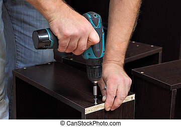 Hands carpenter with screwdriver, tighten screw in drawers...