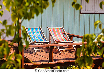 Deckchairs - two colorful deckchairs in a thai tropical...