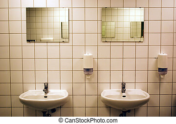 white tiled public bathroom with basins and mirrors