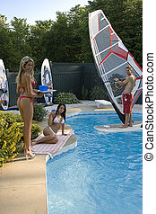Pool party - sexy blond in red bikini serving drinks to a...