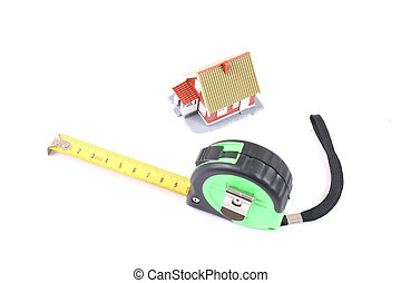The tool for measurement of length and little house over white.