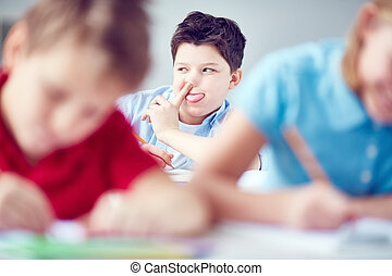 Grimacing - Funny schoolboy grimacing at lesson