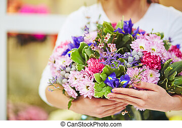 Various flowers - Female florist holding big bouquet of...