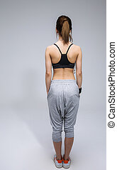 Back view portrait of a young woman in sports wear over gray...