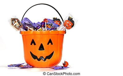 Jack-o-Lantern bucket filled with candies on white...