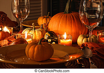 Festive autumn place settings with pumpkins and candles