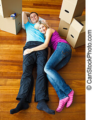 Happy couple relaxing on the floor Moving house - Happy...
