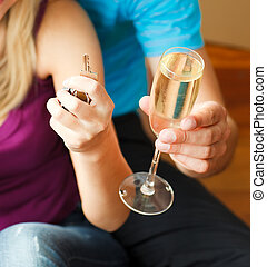 Close-up of couple holding a key and a glass of champagne....
