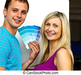 Couple with colour samples to paint new house Concept of...