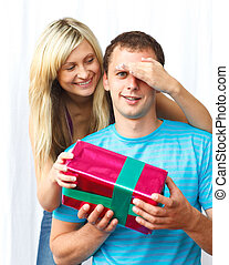 Woman giving a present to her boyfriend and covering his...