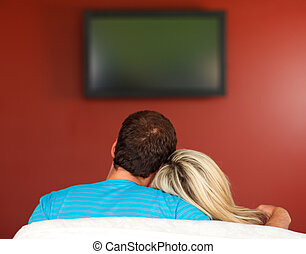 Couple sitting on couch watching a television at home -...