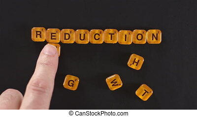 Letters Spelling Weight Reduction - A close up shot of a man...