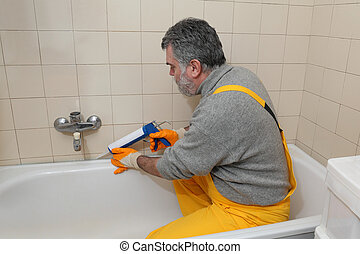 Worker caulking bath tube and tiles - Plumber caulking bath...