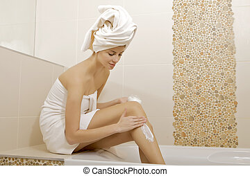 Woman applying moisturizer cream on the legs - Attractive...