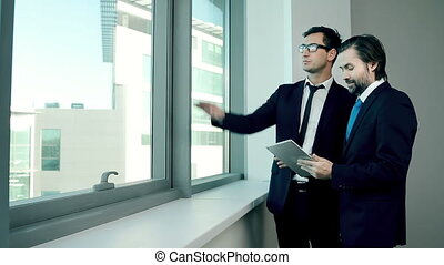 Project Discussion - Two men looking out of the window and...
