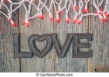Love Text under Red Lights on Rustic Wood