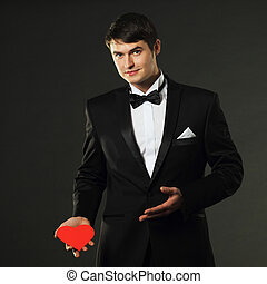 nice handsome man in a tuxedo with a red paper heart On a...