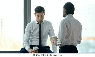 Business Communication - Two office workers talking at the...