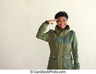 Young woman smiling and saluting - Portrait of a young woman...