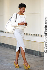 Woman walking and sending text message on mobile phone -...