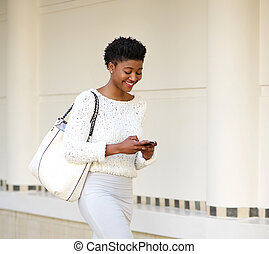 Smiling woman sending text message on mobile phone - Close...