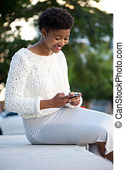 African american woman sending text message with cellphone -...