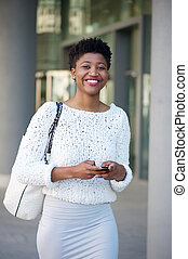 Smiling young woman sending text message int he city -...
