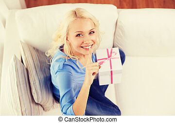 smiling woman with gift box at home - holiday, celebration,...