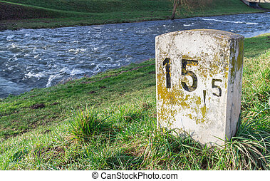 Old Milestone at the river - Old milestone on a sunny and...