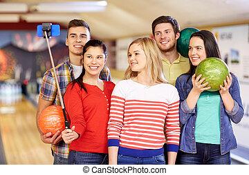 happy friends taking selfie in bowling club - people,...